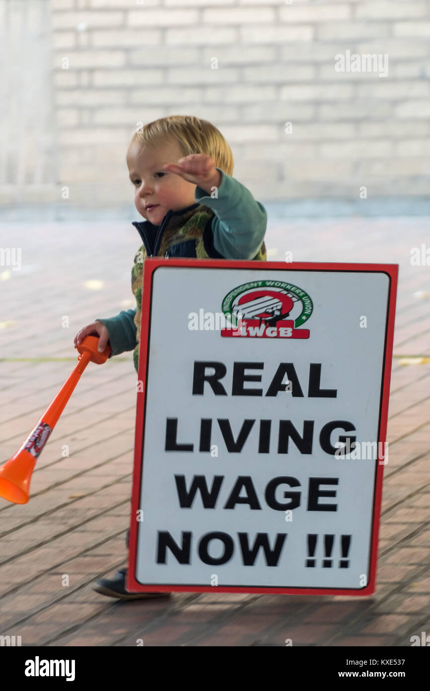 A young IWGB protester who has strayed onto the forecourt of Southwark Crown Court makes the mistake of dropping - Stock Image