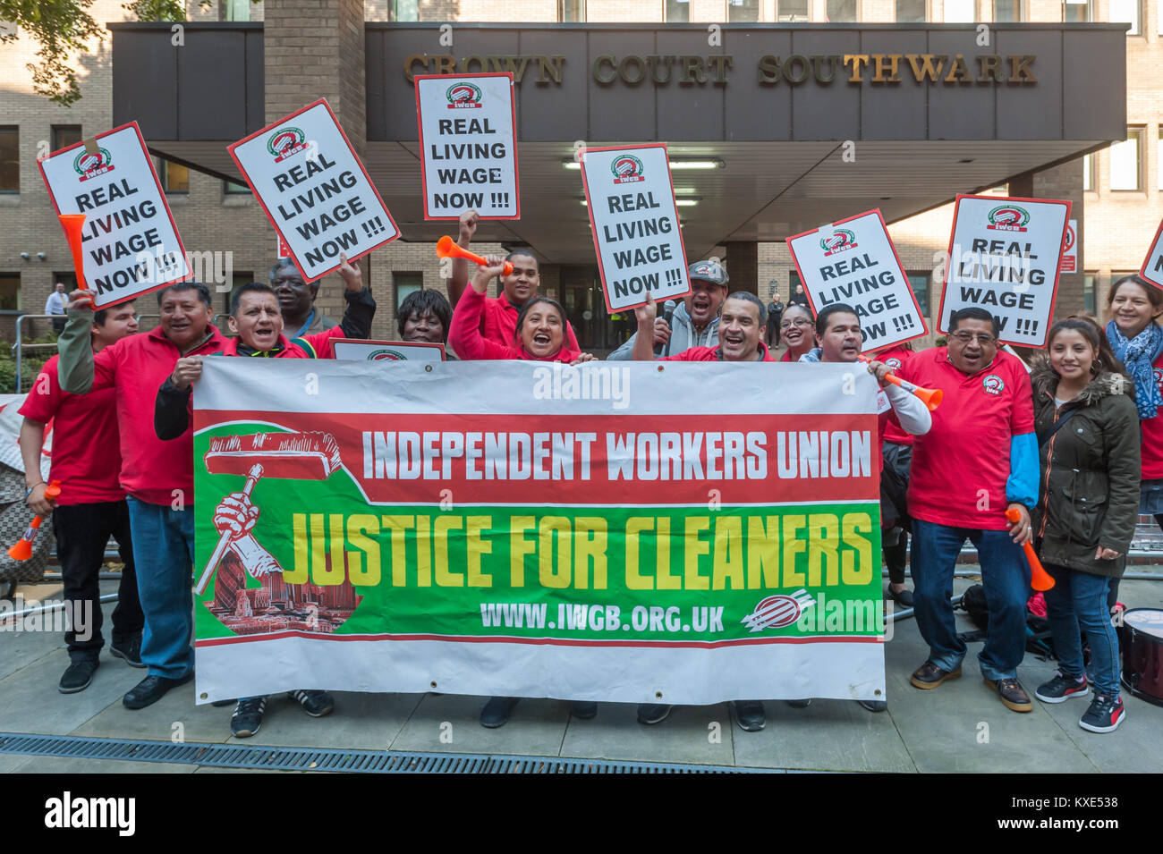 IWGB protesters pose behind the banner 'Justice for Cleaners' outside Southwark Crown Court. They are demanding - Stock Image