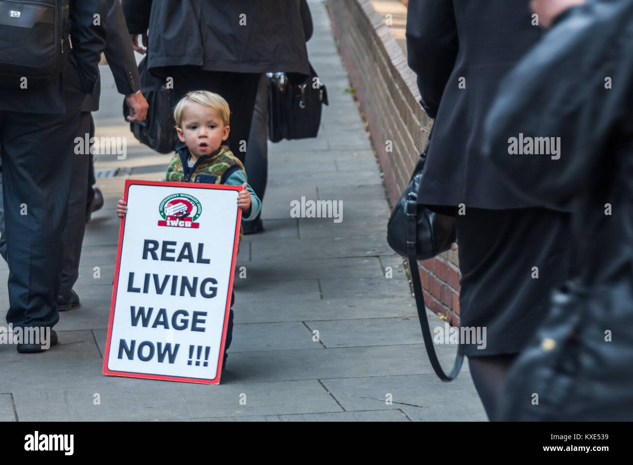 Lawyers with bulding briefcases walk pas a young IWGB supporter holding a placard 'Real Living Wage Now' - Stock Image