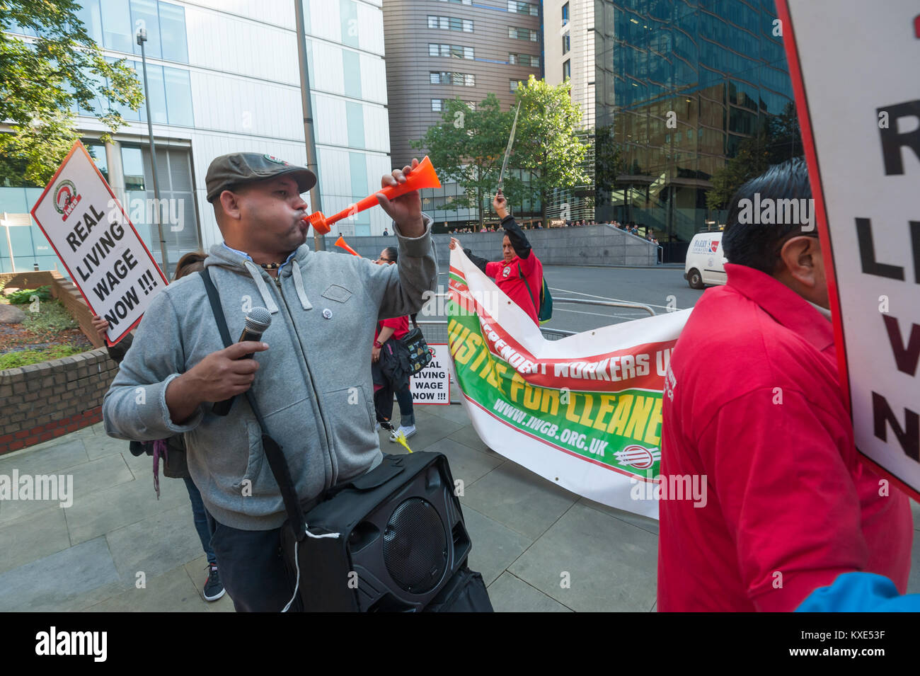 IWGB General Secretary Alberto Dutango blows a horn at the protest for the London living wage for Mitie-employed - Stock Image