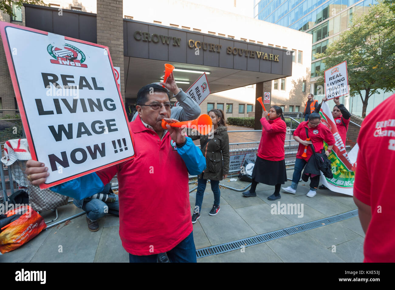 Protesters blow horns at a noisy IWGB protest demanding the London living wage for cleaners at Southwark Crown Court. - Stock Image