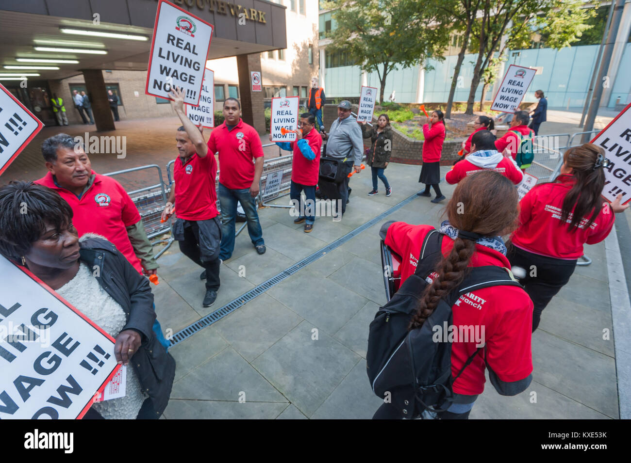 Protesters blow horns and carry posters in a circle at a noisy IWGB protest outside Southwark Crown Court demanding - Stock Image