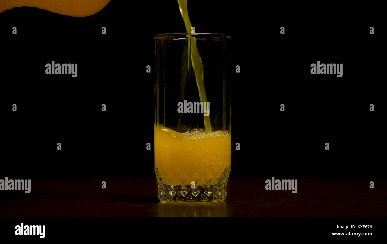 Orange soda large glass, overflowing glass of orange soda closeup with bubbles isolated on black background. Pouring - Stock Image