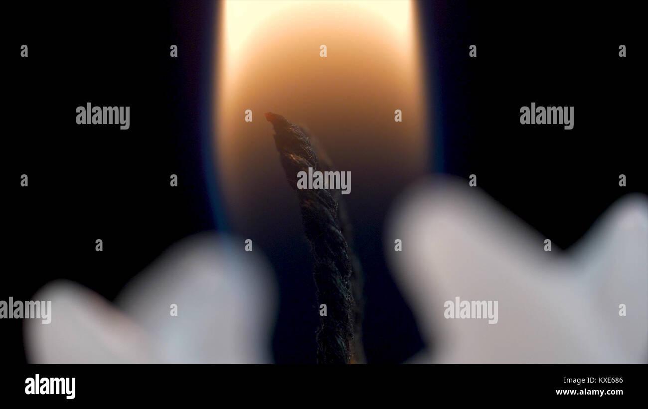 White long candle on black background. Single candle flame light. Long flame, old candle. White candle, black background. Stock Photo