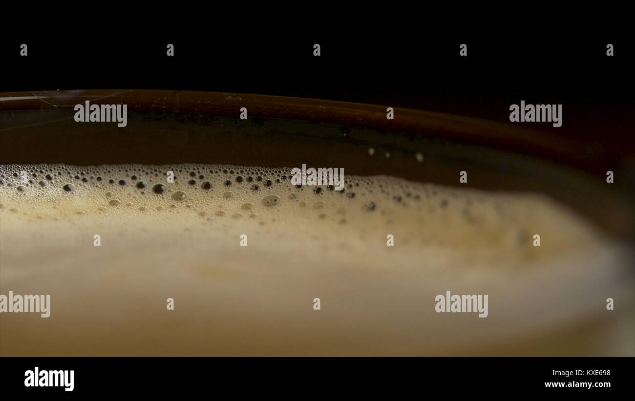 Close-up of coffee foam isolated over a black background, viewed from top. Black espresso coffee with heady froth - Stock Image