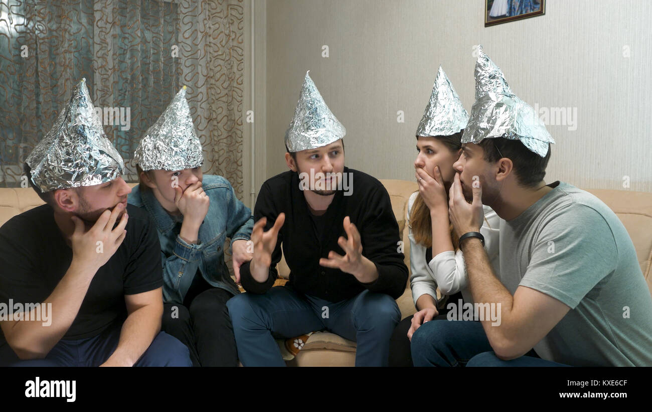 Group of people with foil on their heads discussing conspiracy theories. Friends with foil on their heads. You know, - Stock Image