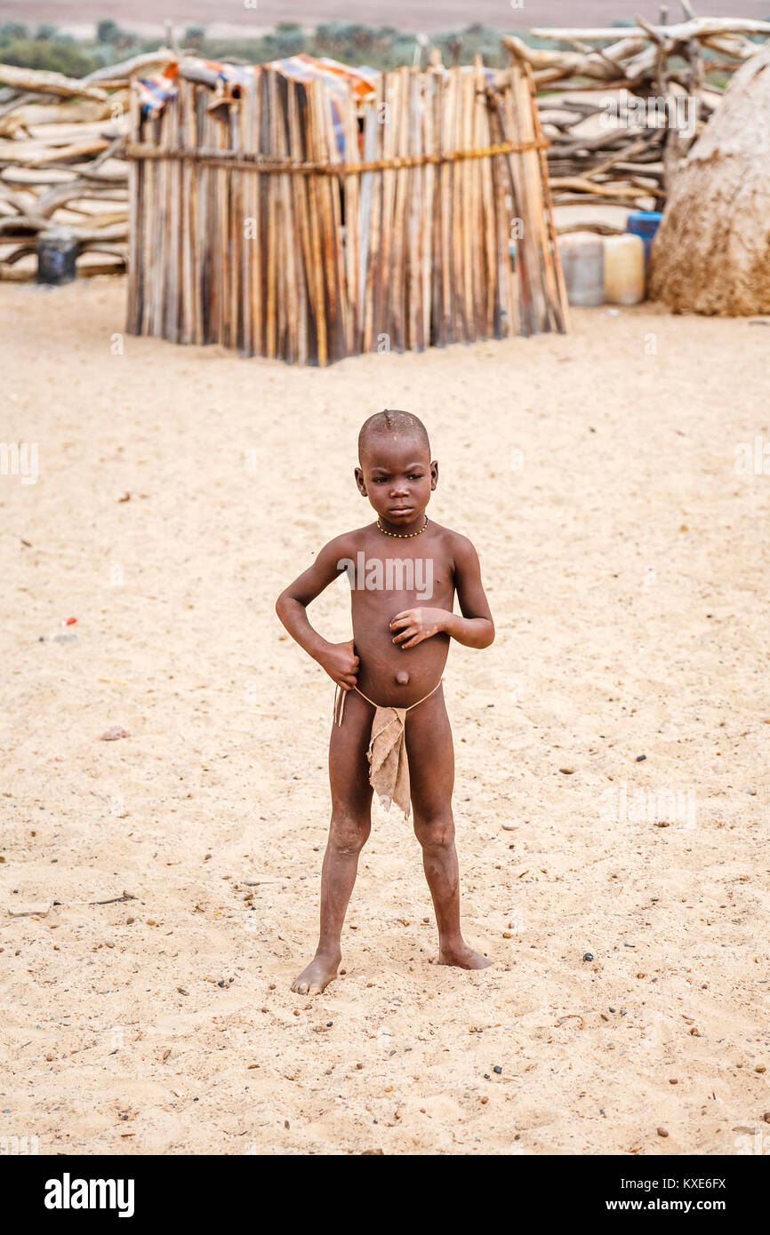 Small child of the Himba tribe people indigenous to the Kunene Region of northern Namibia, south-west Africa standing Stock Photo