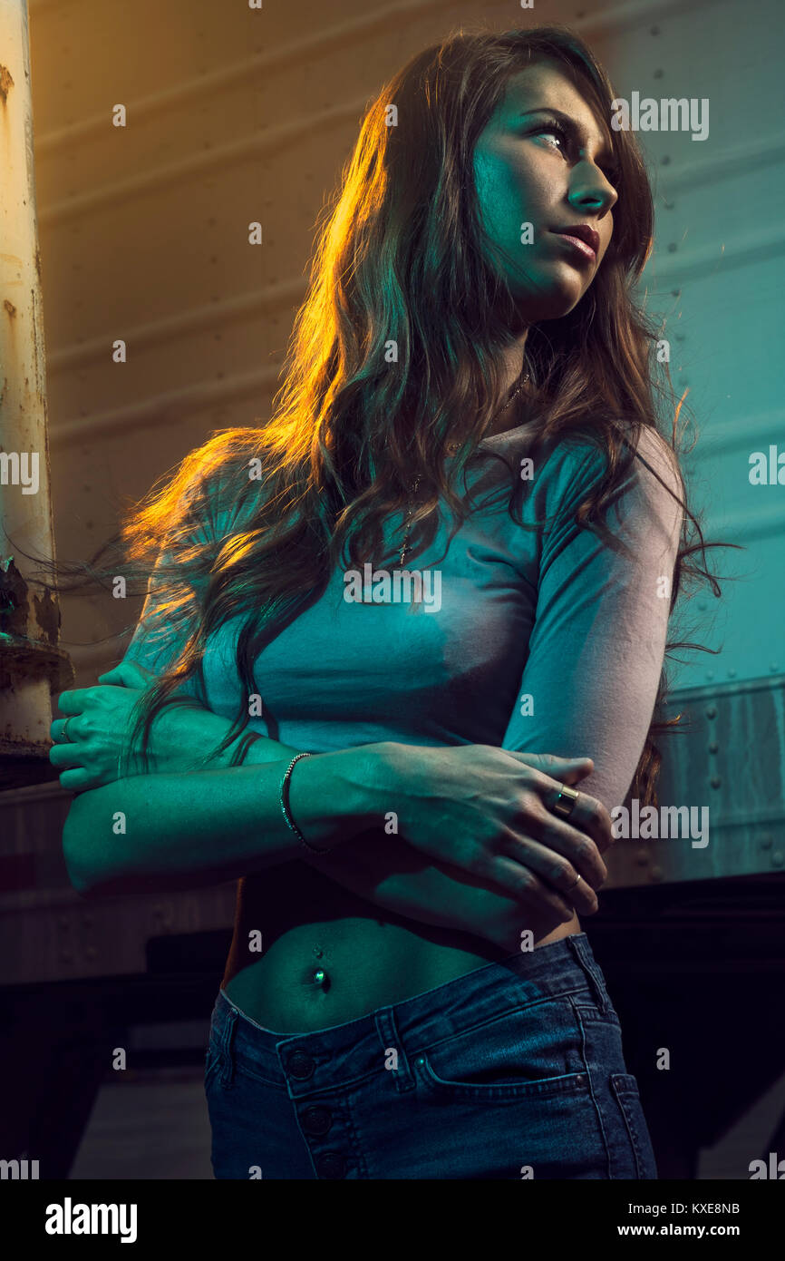Young woman standing and hiding around semi trailers - Stock Image