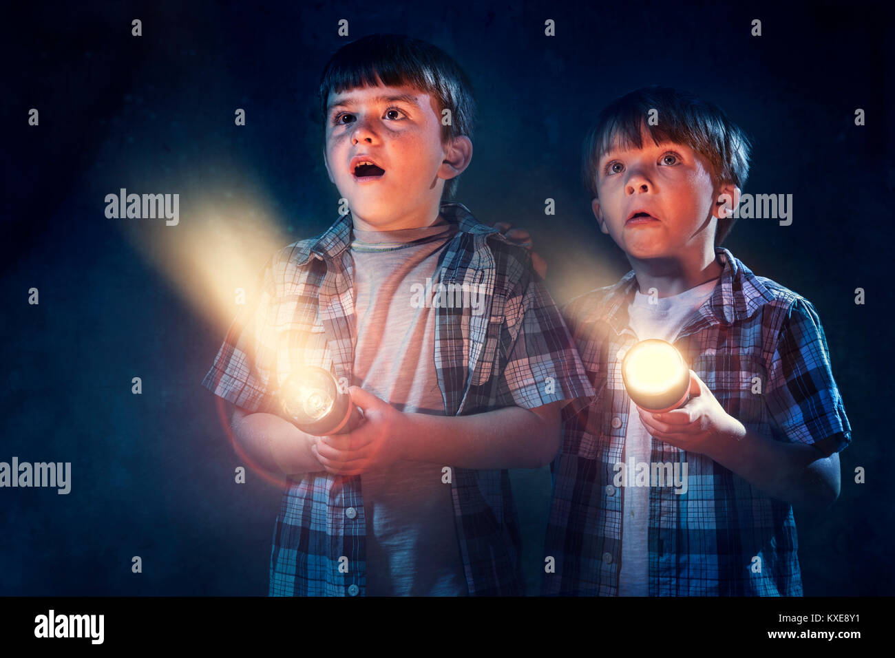 Young boys scared in dark with flashlight - Stock Image