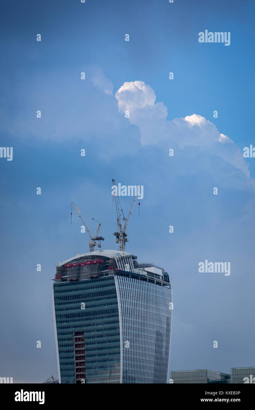 Cranes on top of 20 Fenchurch St reach towards the clouds - Stock Image