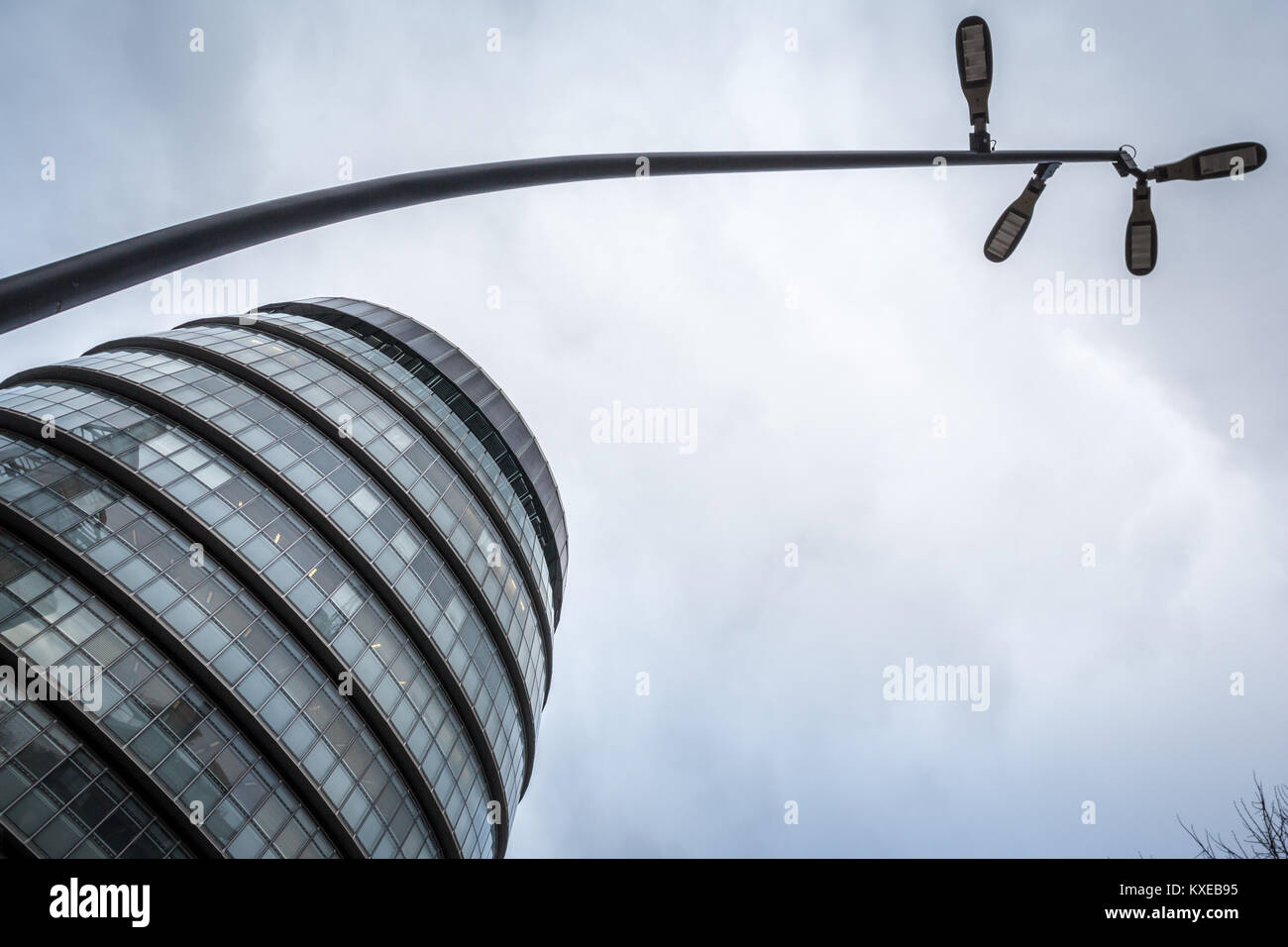 A street lamp curves into the sky next to Londons City Hall where the Mayor of London works - Stock Image
