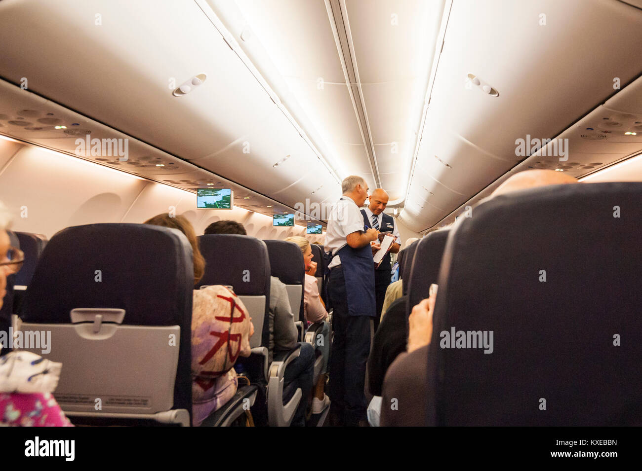 Cabin crew serving drinks on a Boeing 737 in flight on a TUI plane - Stock Image