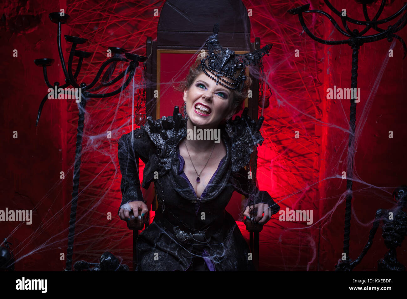 Woman in black sits on a throne in a red room and growls. - Stock Image