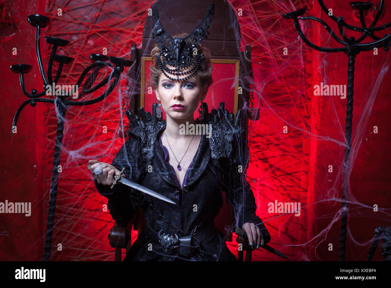 Woman in black sits on a throne and holds a dagger in her hands. - Stock Image