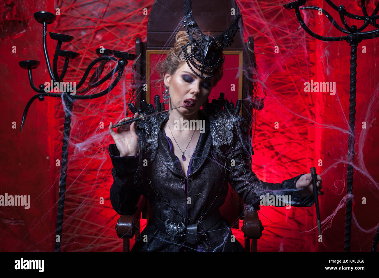 Woman in black sitting in a dark red room. She licks a dagger. - Stock Image