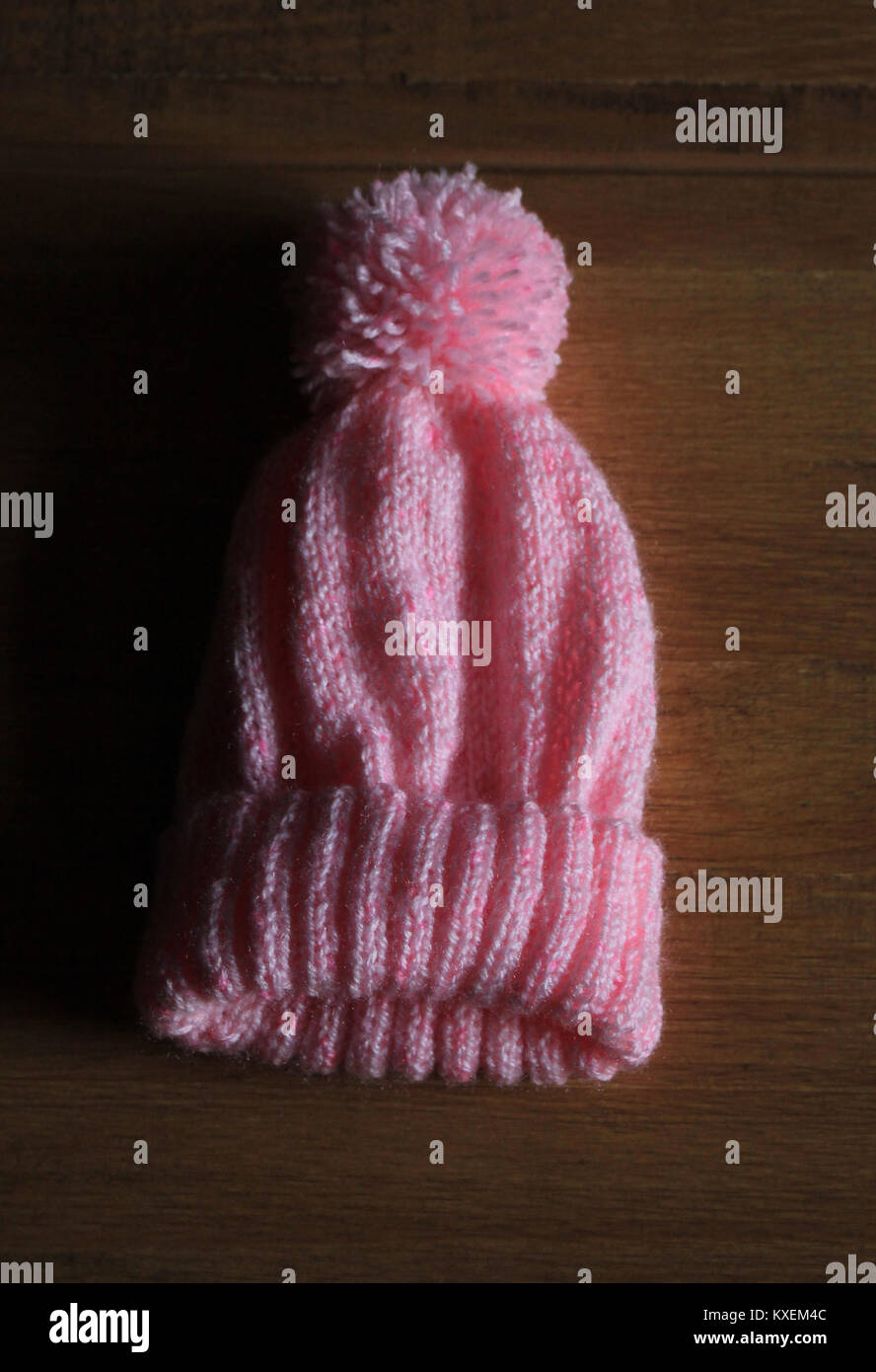 A Pink Baby's Bobble Hat hand knitted by Carole Wareing displayed on a dark background with the light coming in - Stock Image