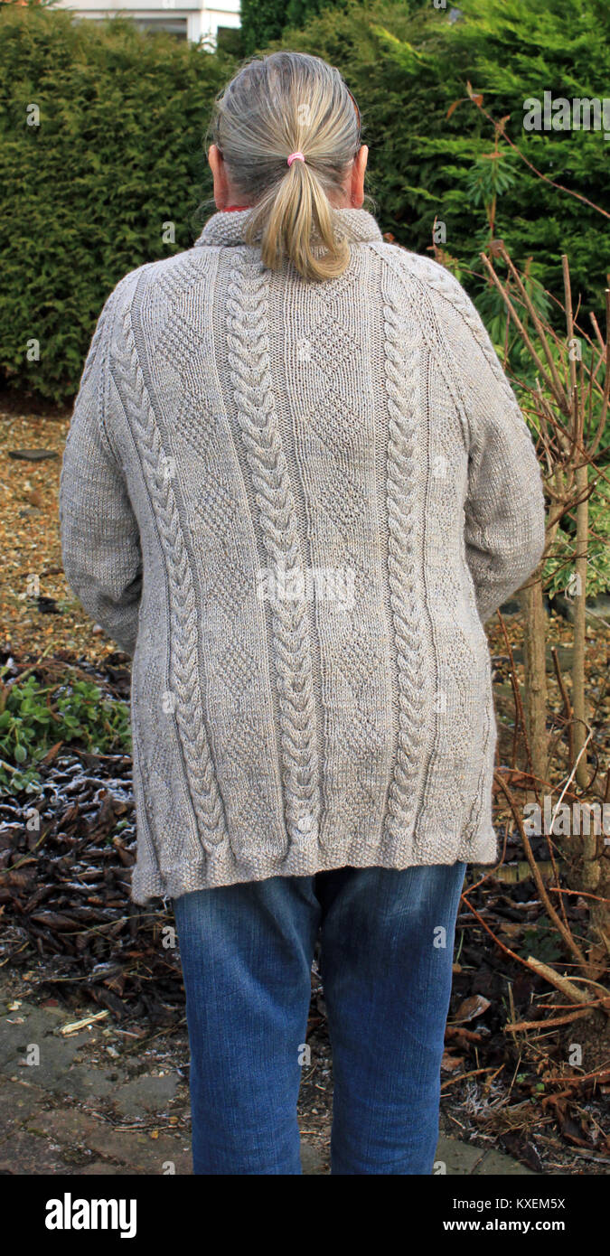 A lady displays an edge to edge cardigan hand knitted, by Carole Wareing. Created from Double Knitting with Merino - Stock Image