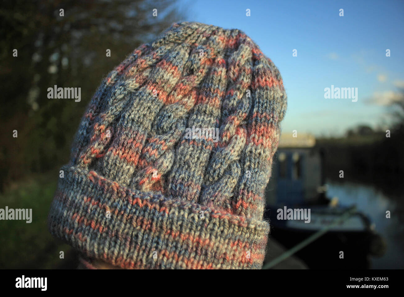 A lovely soft hand knitted adult's beanie type hat which is knitted from a yarn that has grey and pink shades with - Stock Image
