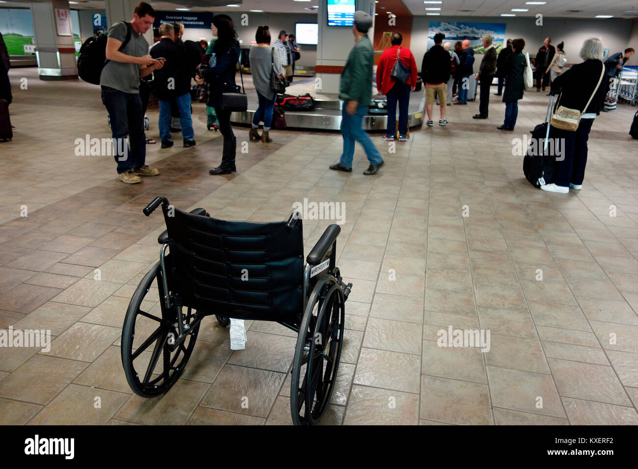 A wheelchair in an airport baggage claim area - Stock Image