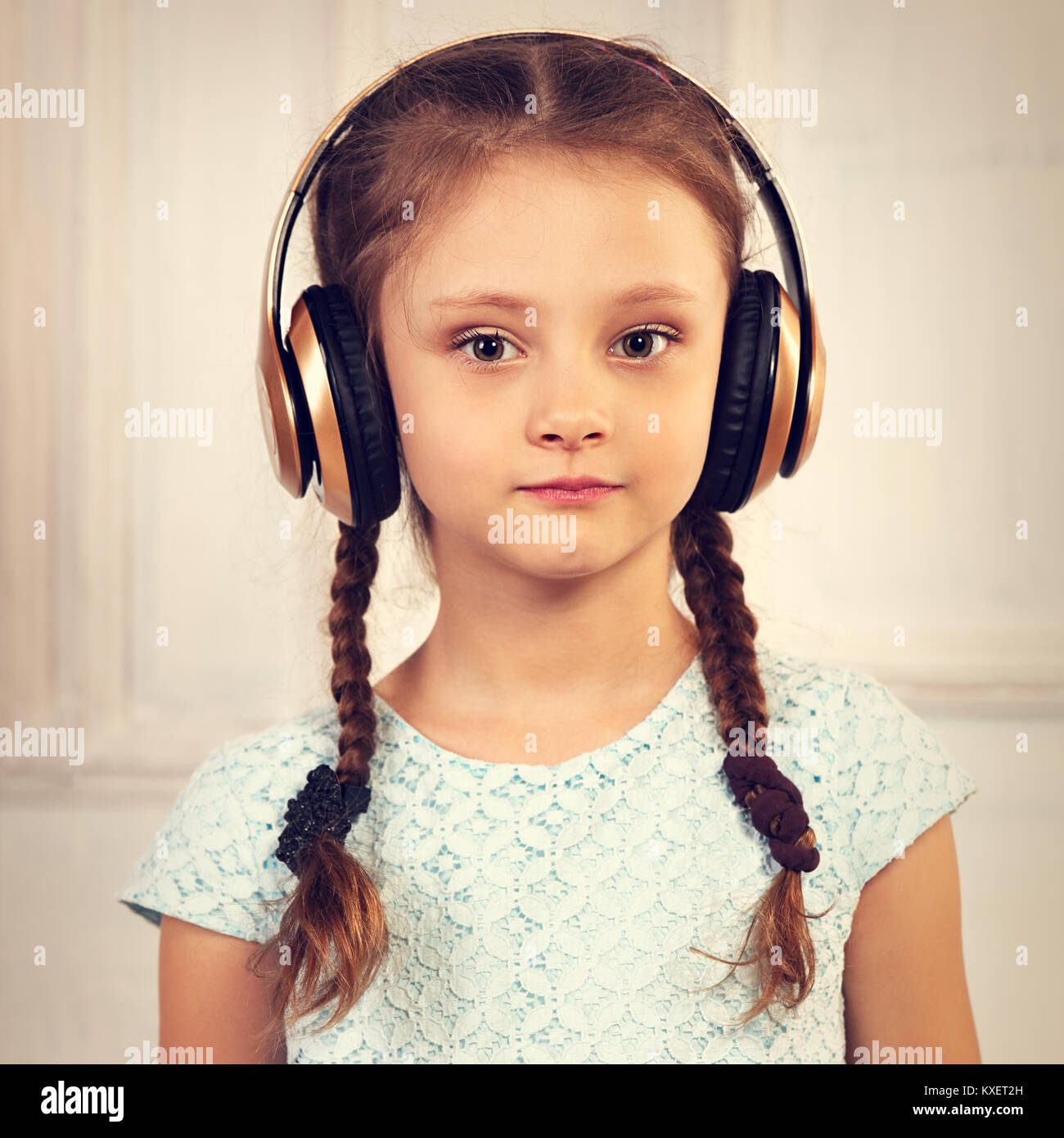 Happy calm serious kid girl in blue dress listening the