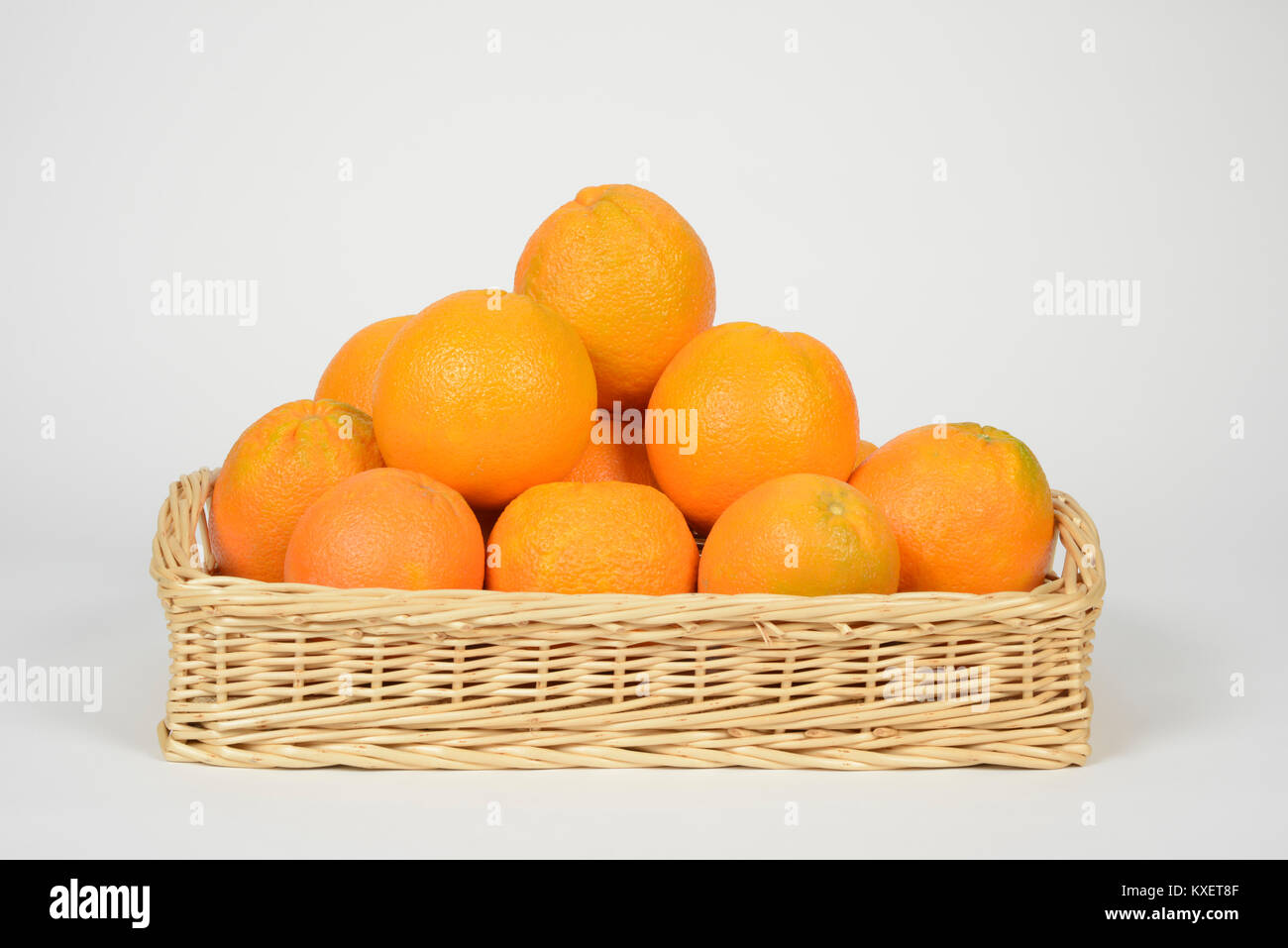 Oranges in a basket on white background - Stock Image