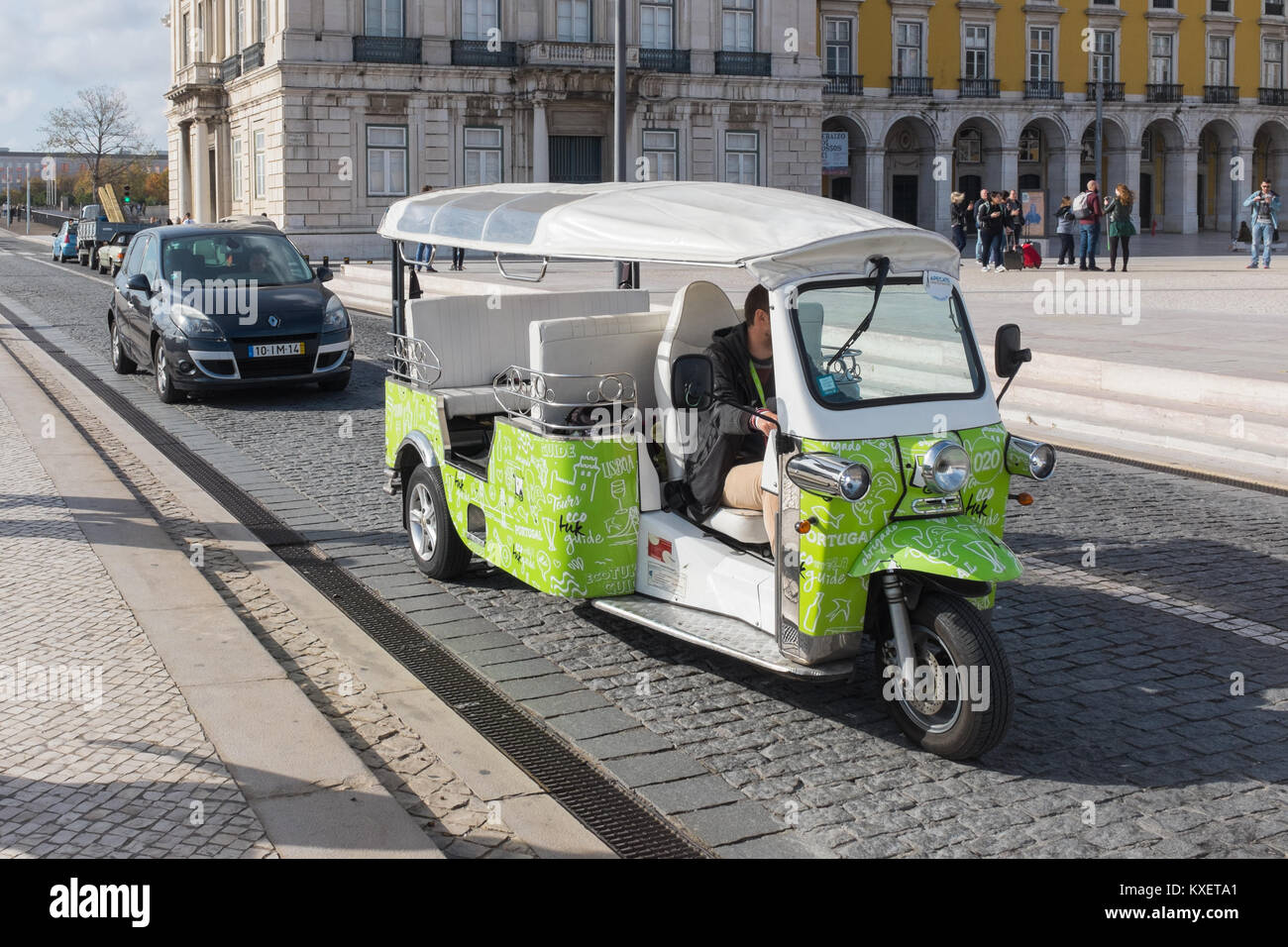 Eco-friendly tuktuk giving tourists guided tour around Lisbon, Portugal - Stock Image
