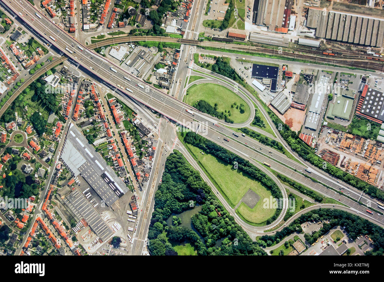 Aerial view over ribbon building and highway interchange / motorway interchange with slip roads leading to industrial - Stock Image