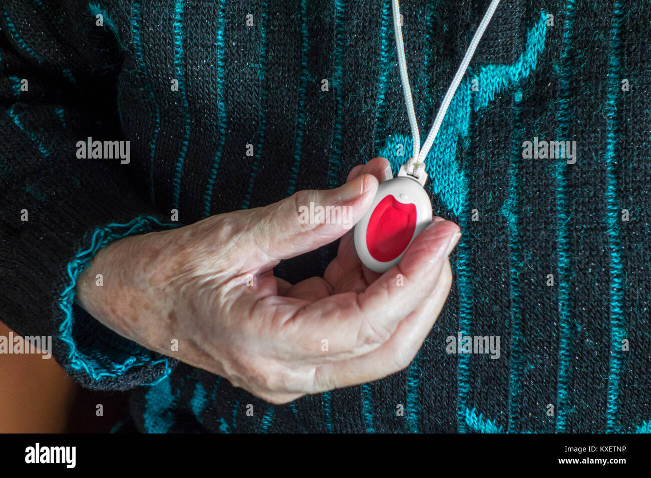 Close up of hand holding life saving personal alarm for the elderly close up of hand holding life saving personal alarm for the elderly and disabled people showing pendant with push button aloadofball Images