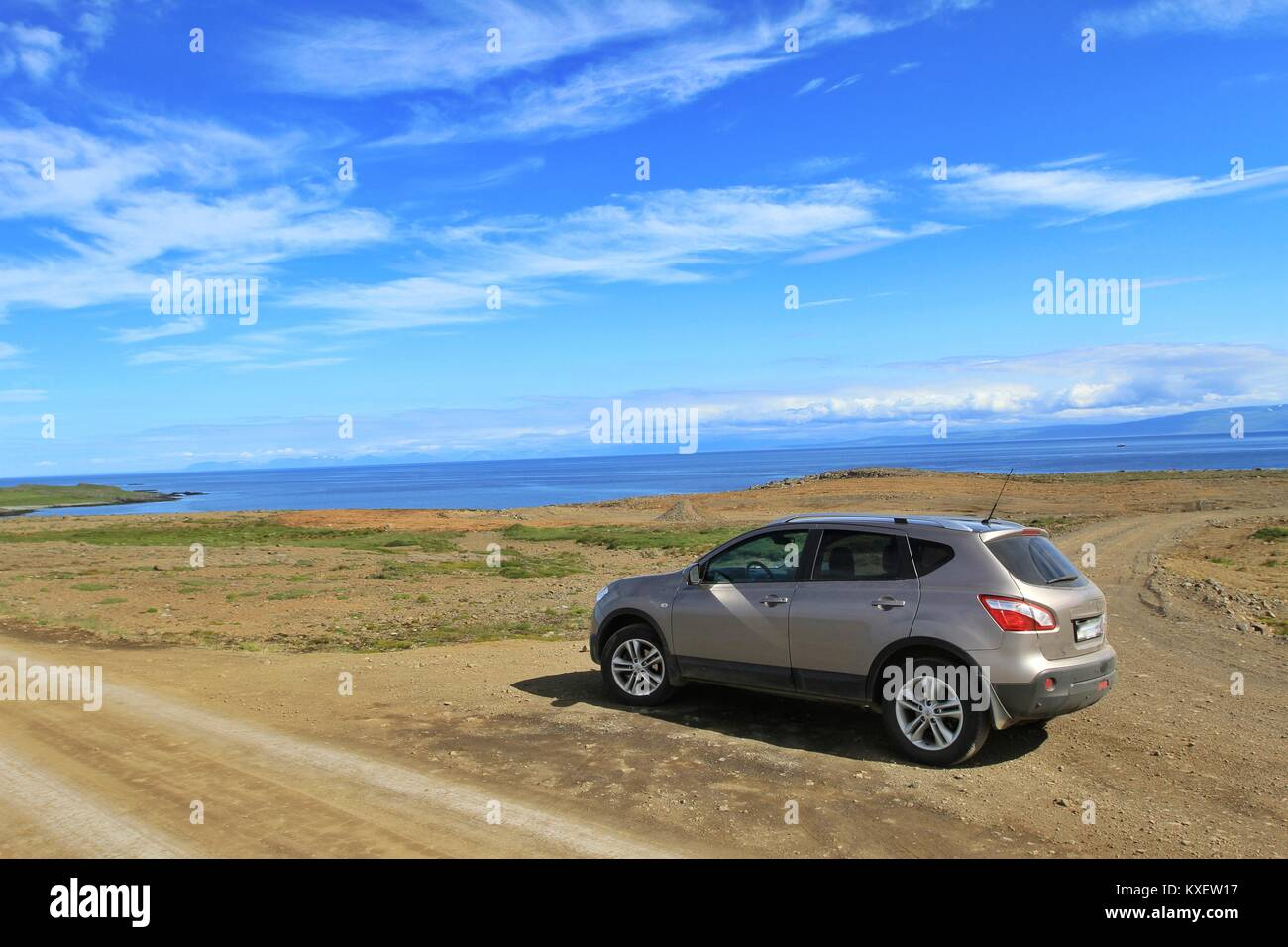 Parked car in Iceland on a Dirt Raod Ocan in Background - Stock Image