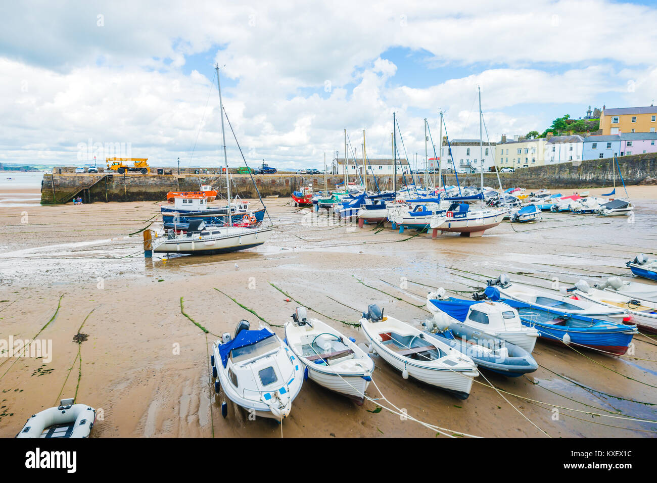 Boats on the sandy beach at low tide in Tenby bay, Wales - Stock Image