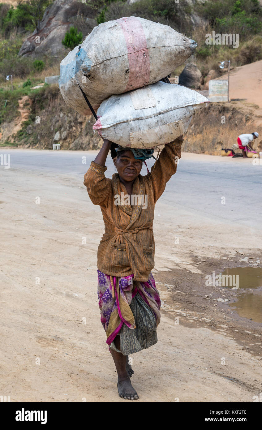 A local woman with carrying two big sacks of charcoal over her head. Madagascar, Africa. - Stock Image