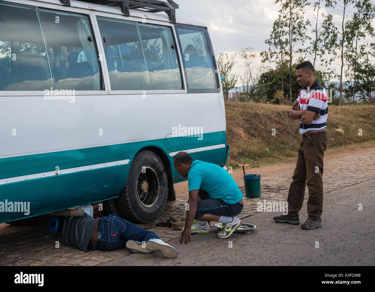 A man is under a minibus, trying to fix a flat tire, on the side of road. Madagascar, Africa. - Stock Image