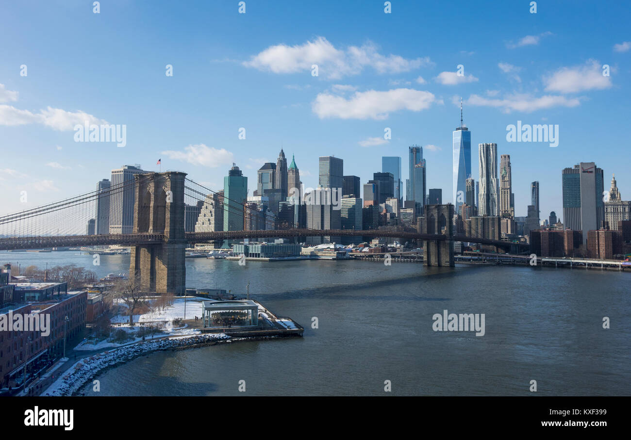 The Brooklyn Bridge and Lower Manhattan skyline seen from the Brooklyn side of the East River in winter - Stock Image