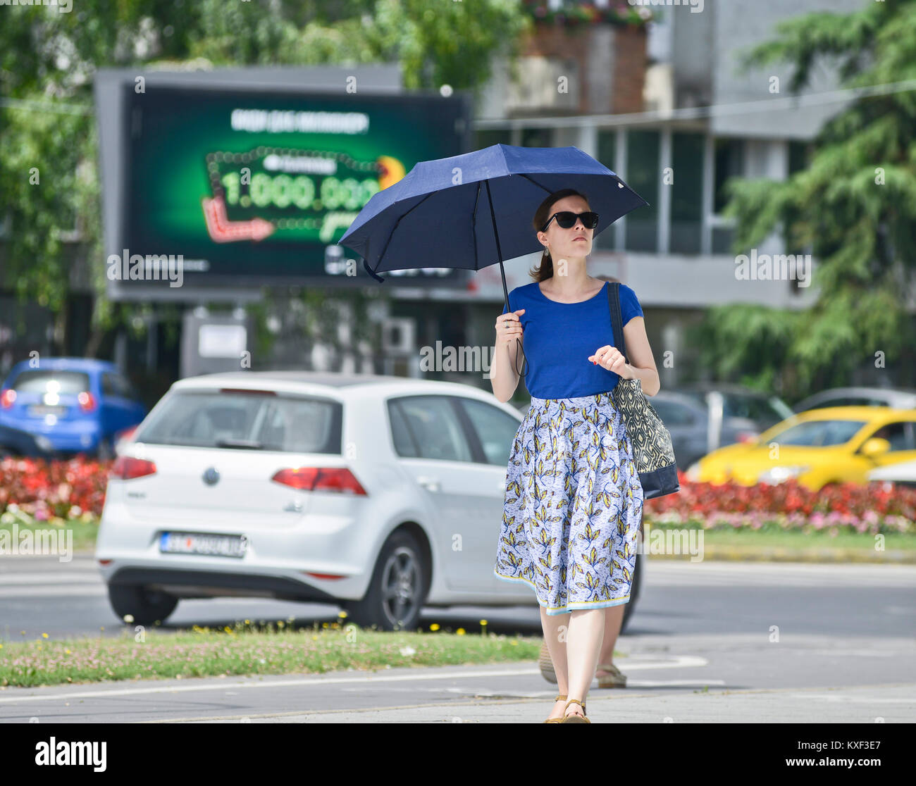 A woman walking under the sun with umbrella and sunglasses, Skopje, Macedonia - Stock Image