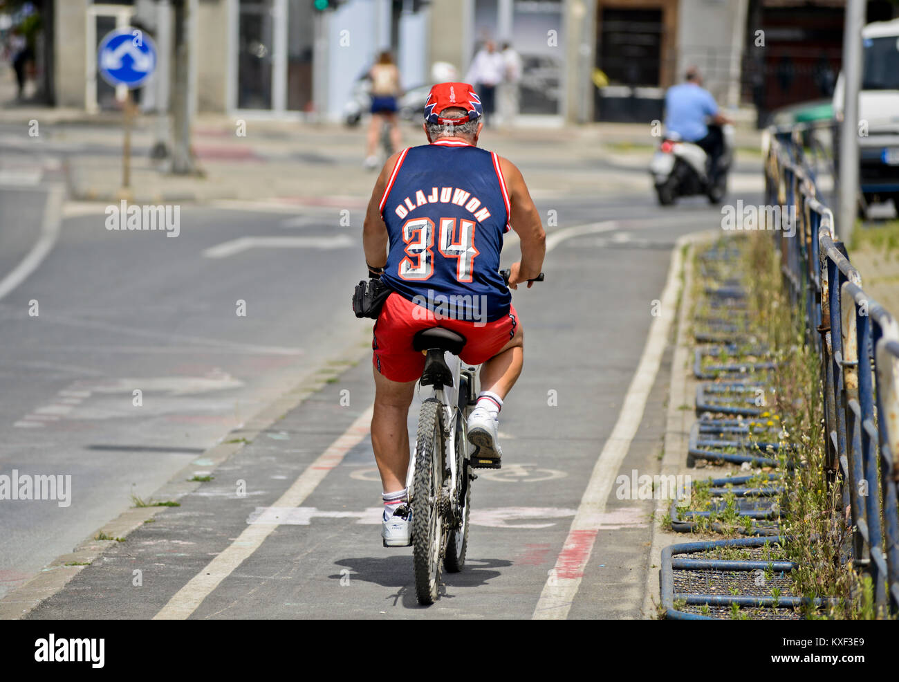 A man riding a bike wearing a basketball jersey (Hakeem Olajuwon, Houston Rockets). Skopje, Macedonia - Stock Image