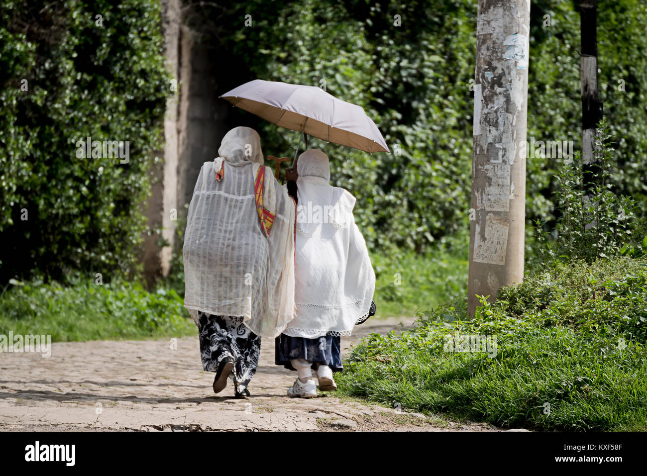 Two Ethiopian Orthodox women wearing white capes heading towards church with umbrella in Addis Ababa Ethiopia - Stock Image