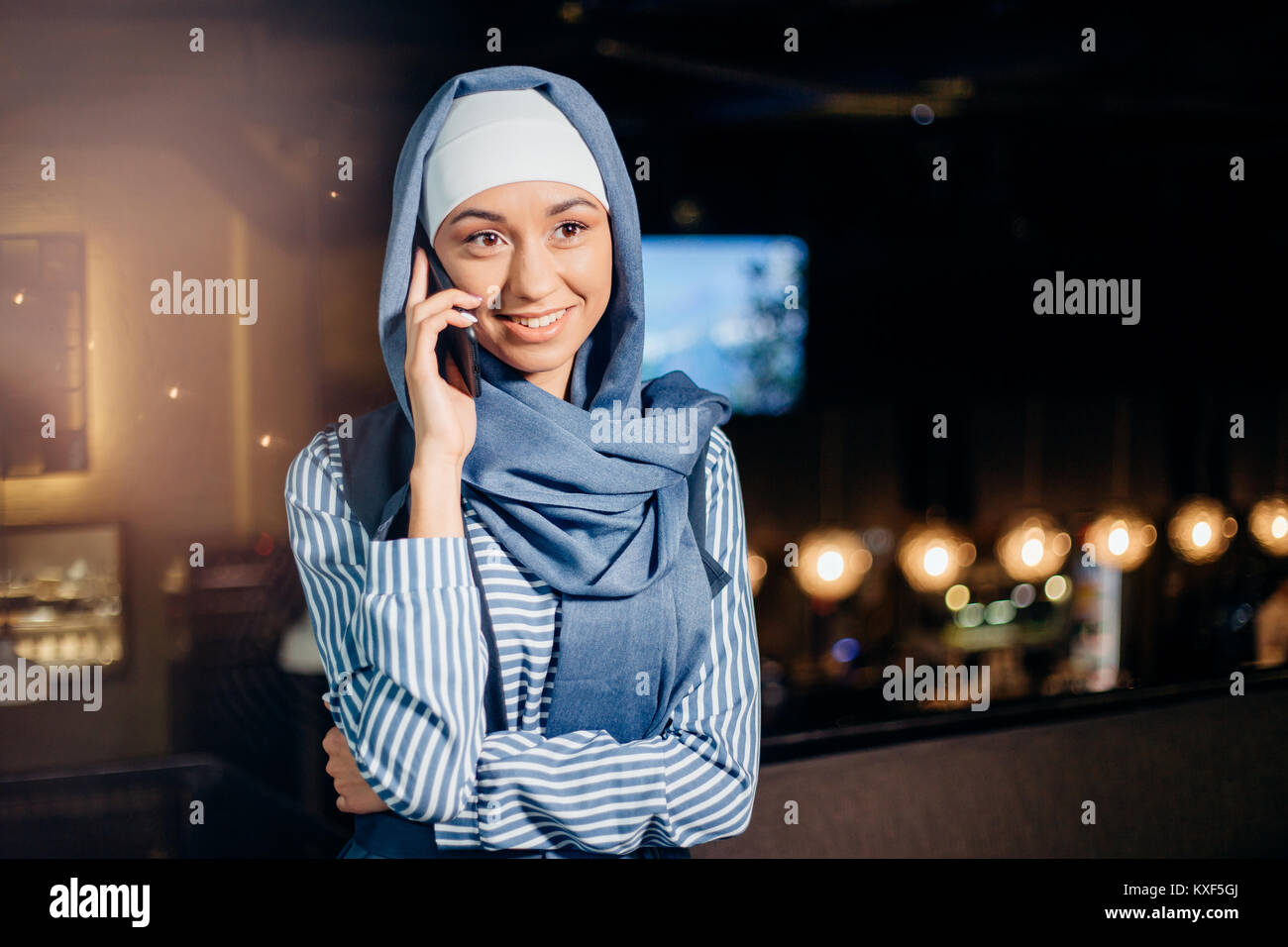 Muslim business woman on phone over conference - Stock Image