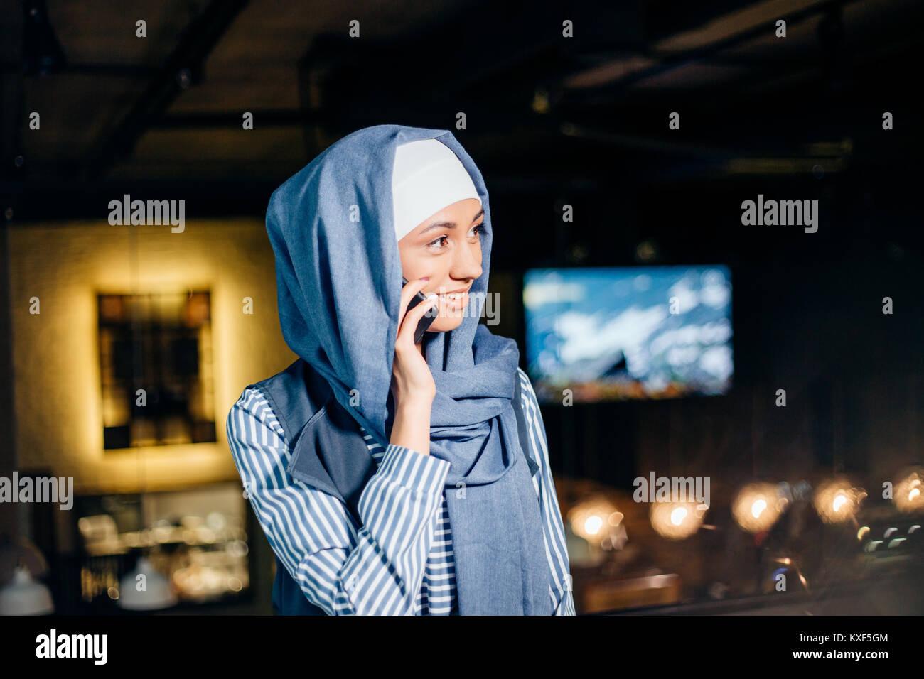 Muslim Woman On Break Using Mobile Phone In cafe - Stock Image