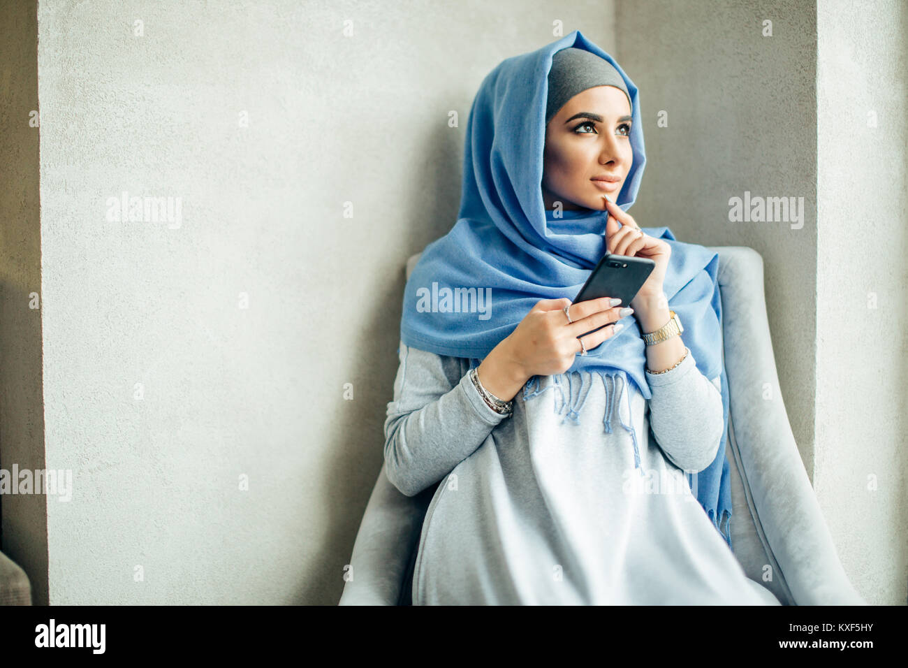 Muslim woman messaging on a mobile phone in cafe - Stock Image