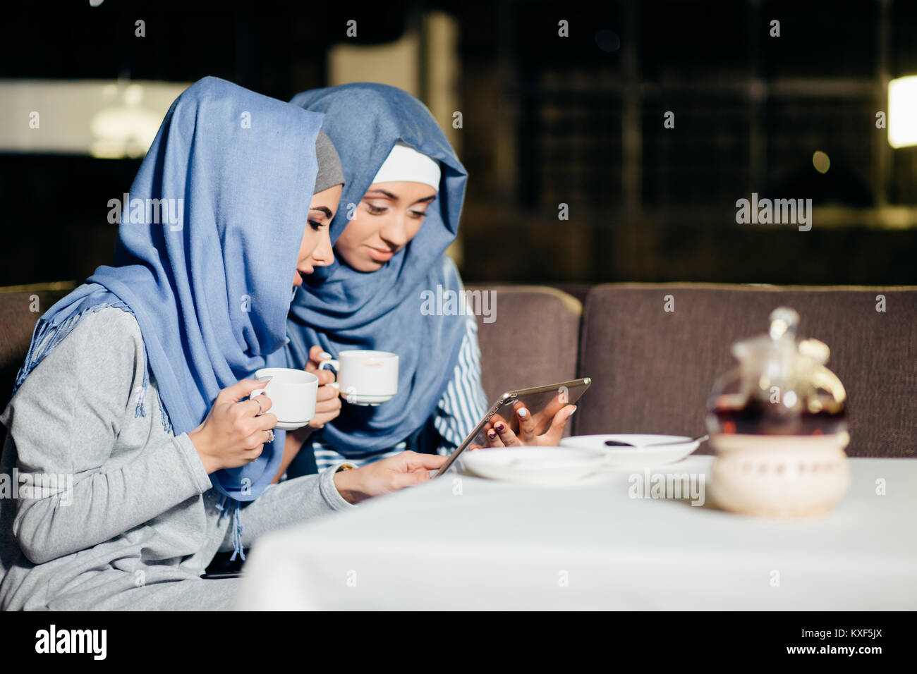 pretty muslim woman use tablet in cafe - Stock Image