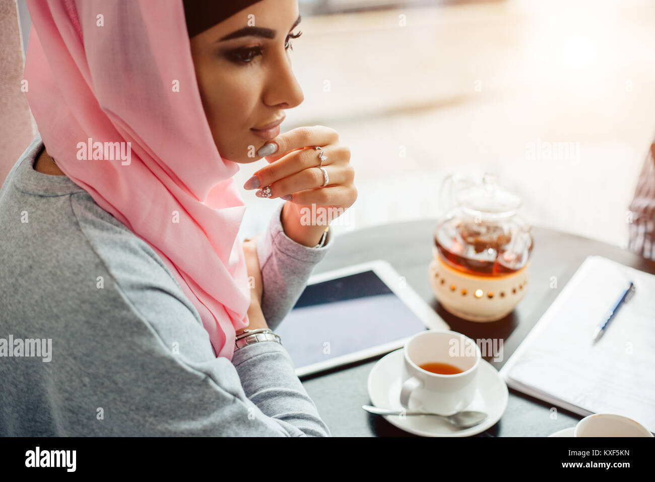 Portrait of a beautiful Muslim woman in cafe - Stock Image