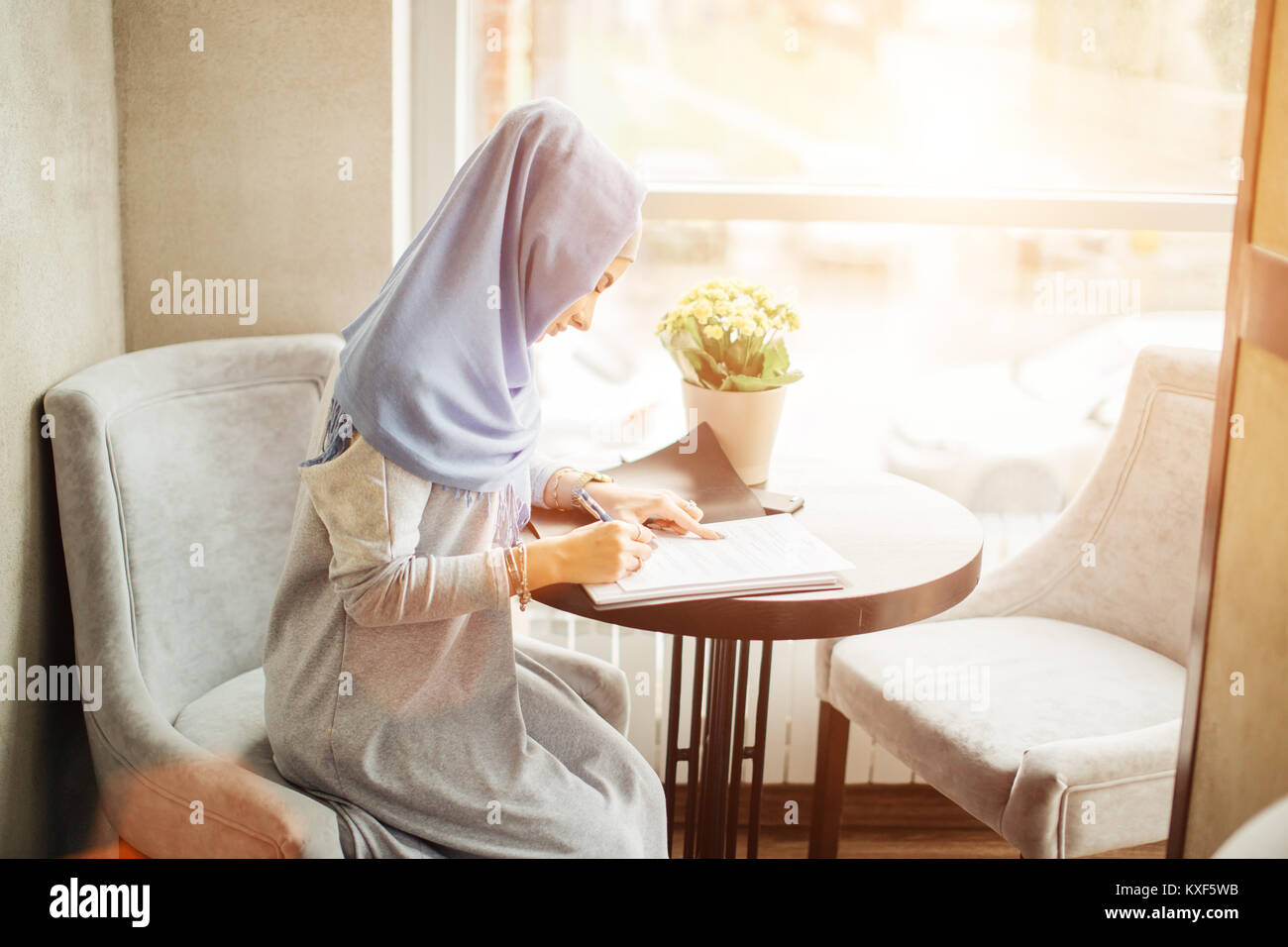 muslim business woman working documents in cafe - Stock Image