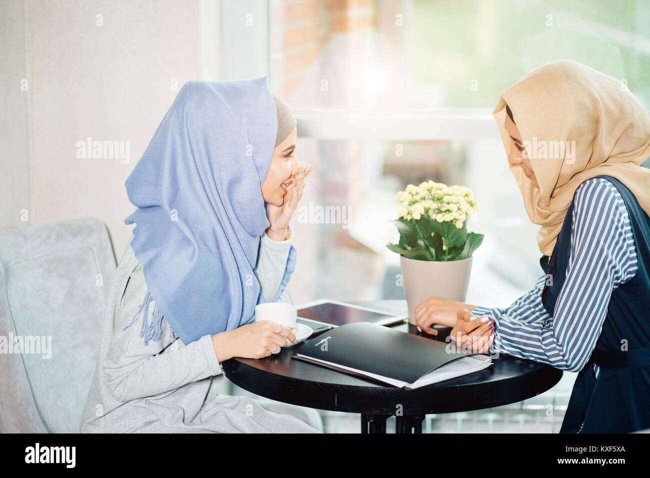 portrait of two woman talking while sitting on couch enjoying coffee - Stock Image
