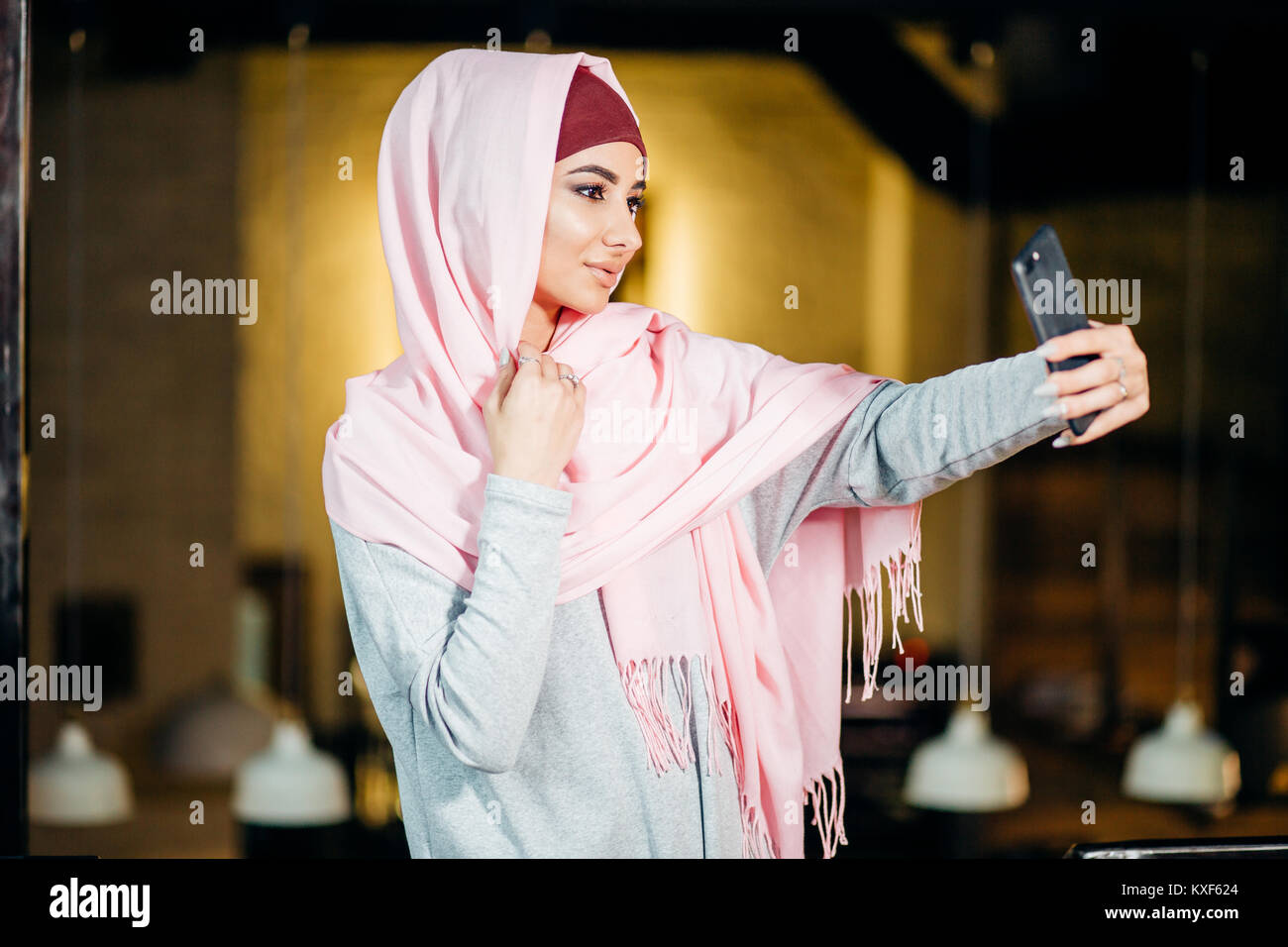 Arabian muslim woman taking selfie with phone in cafe - Stock Image