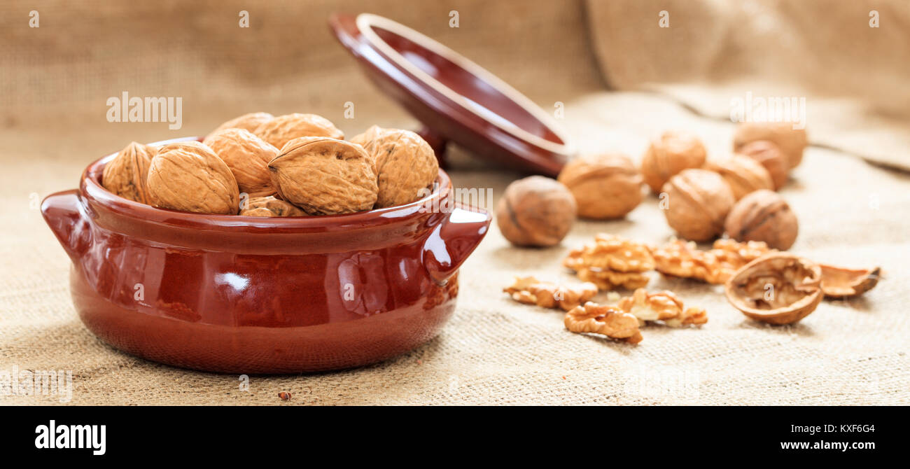 Walnuts in a ceramic pot on a burlap - Stock Image