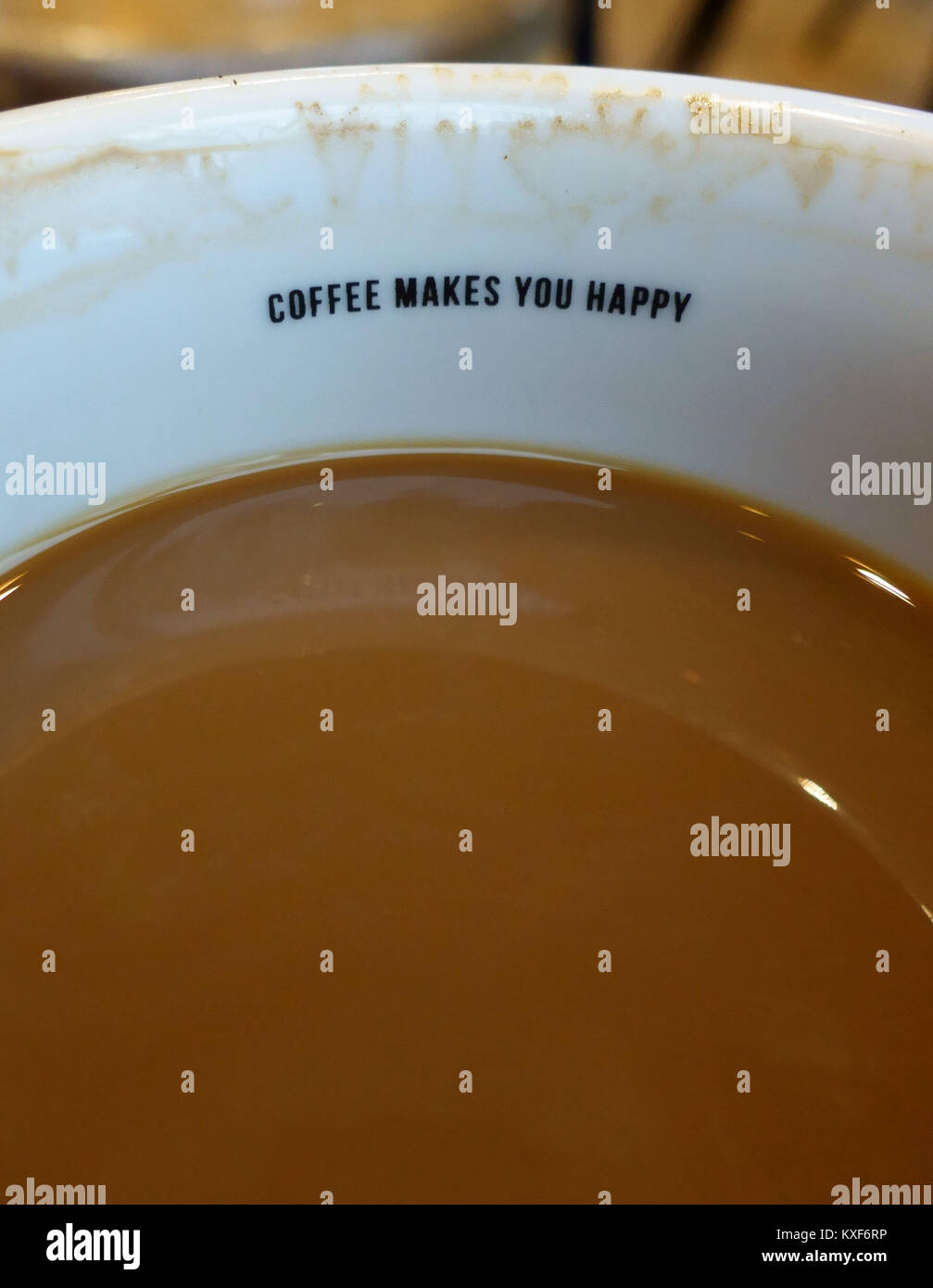 'Coffee Makes You Happy' slogan inside coffee shop cup, London - Stock Image