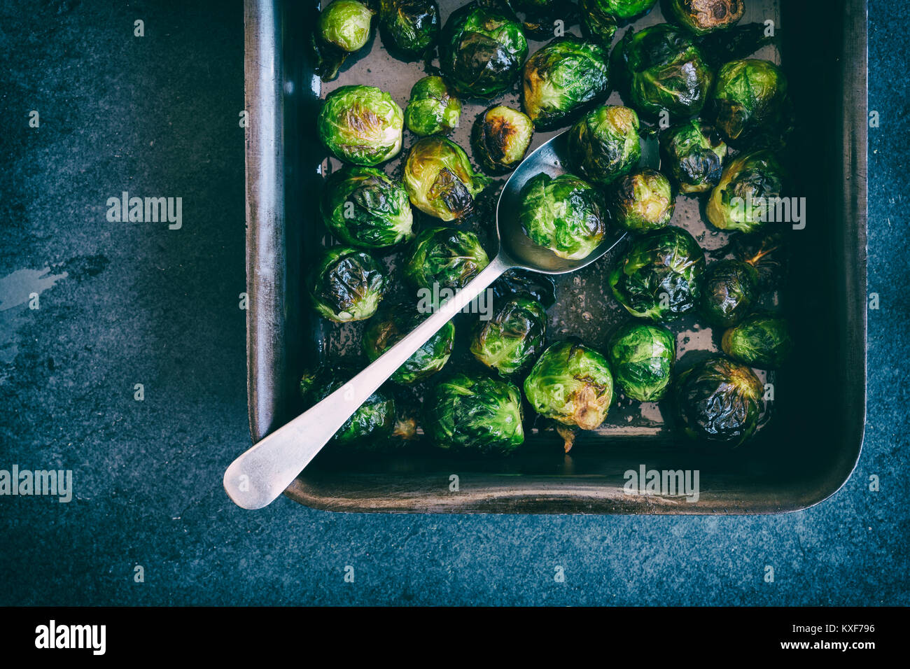 Brassica oleracea. Roasted Brussel sprouts in a baking tray with spoon on a slate background. Vintage filter applied - Stock Image