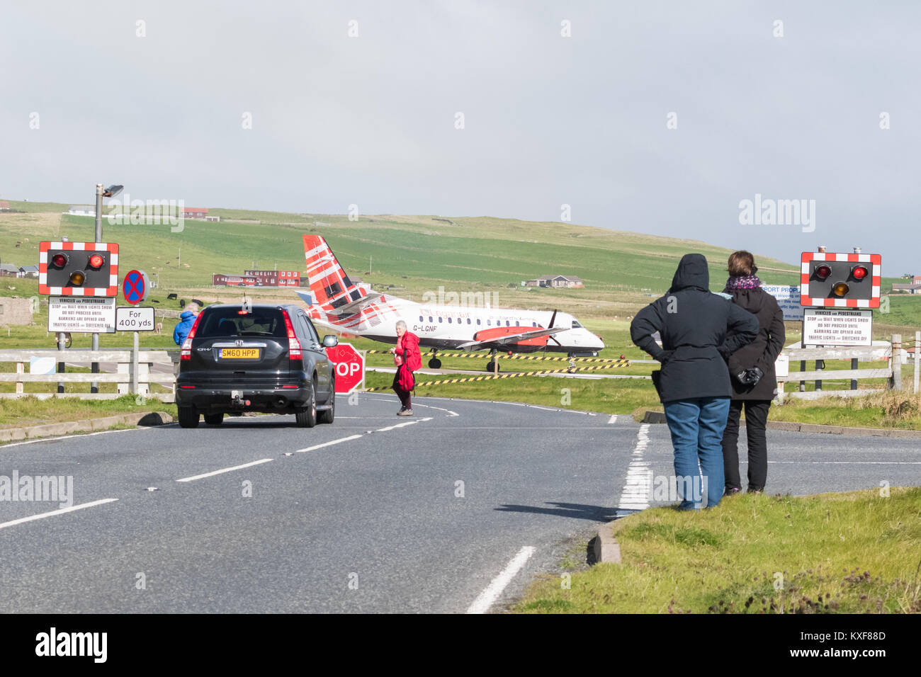 Sumburgh Airport, Shetland Islands, Scotland, UK - road crossing closed to allow Loganair flight to land, watched - Stock Image