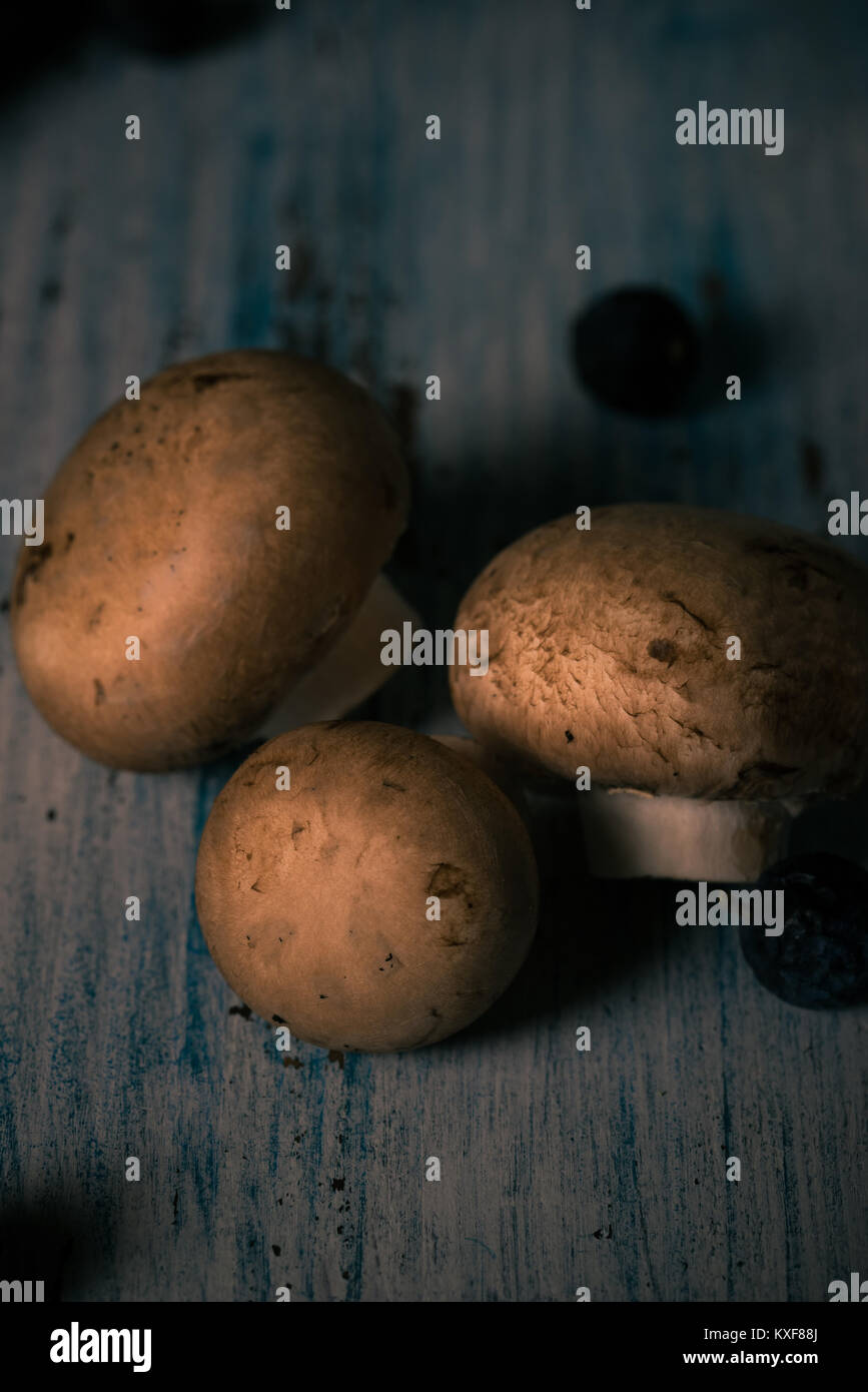 Vertical photo with top view on three edible mushrooms. Champignons with brown cap on vintage wooden board with - Stock Image