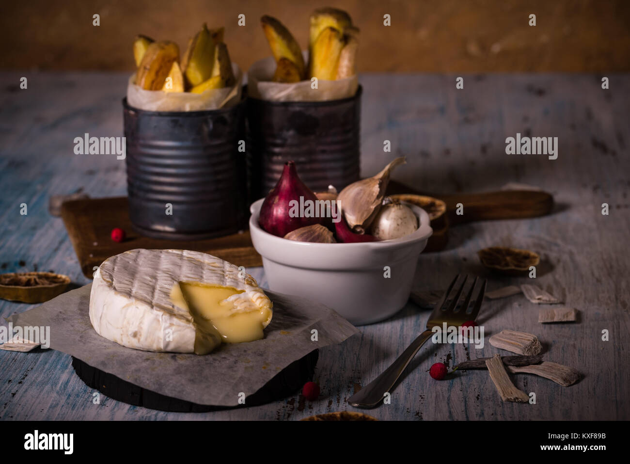 Horizontal photo of hot melted camembert cheese on paper sheet with bowl full of garlic and onions and old vintage - Stock Image